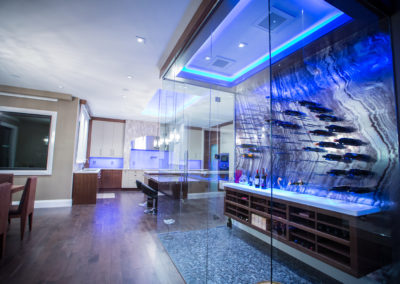 a kitchen and wine fridge with modern lighting