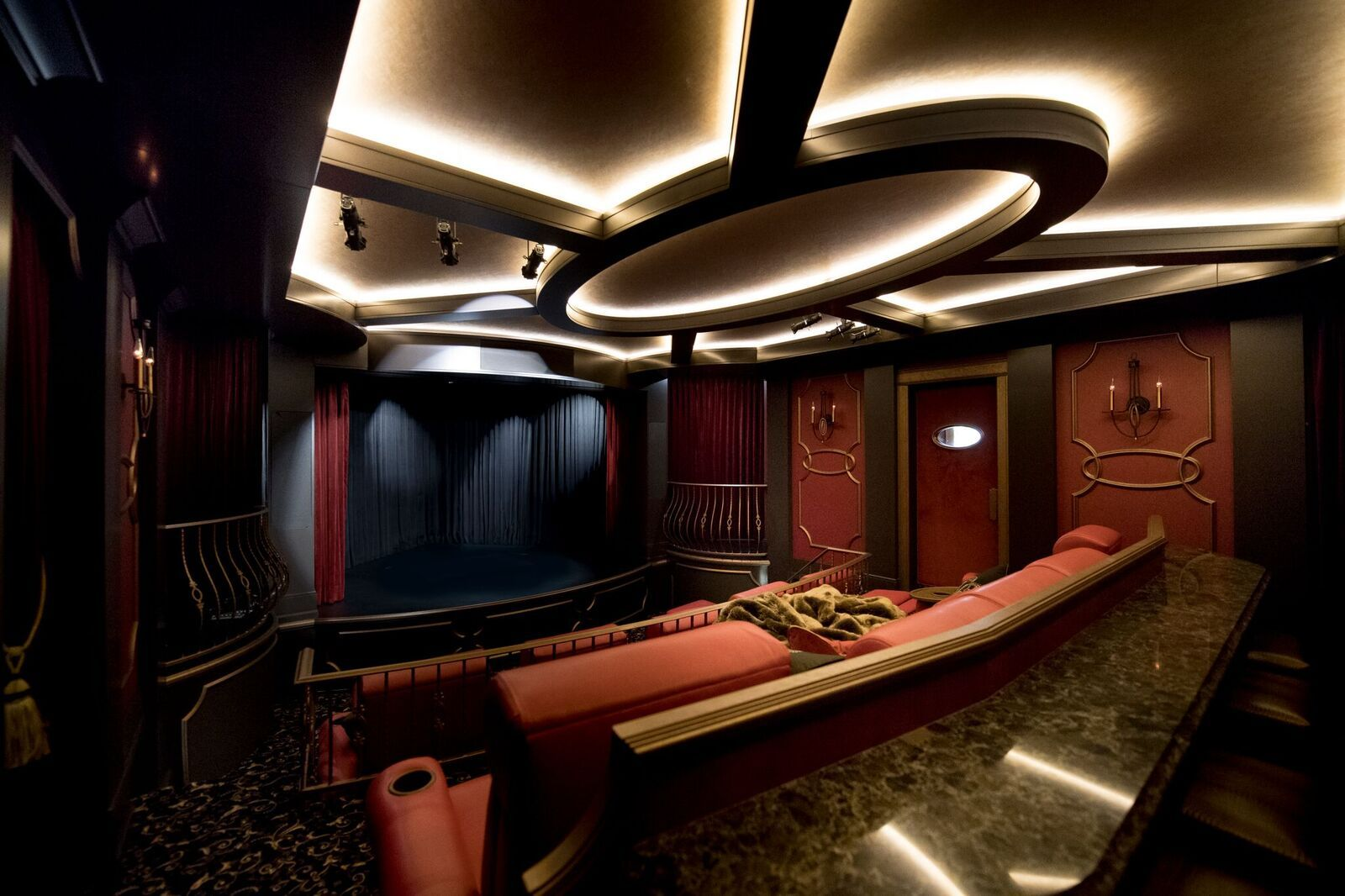 Luxury custom home movie theatre with red seats and black curtain